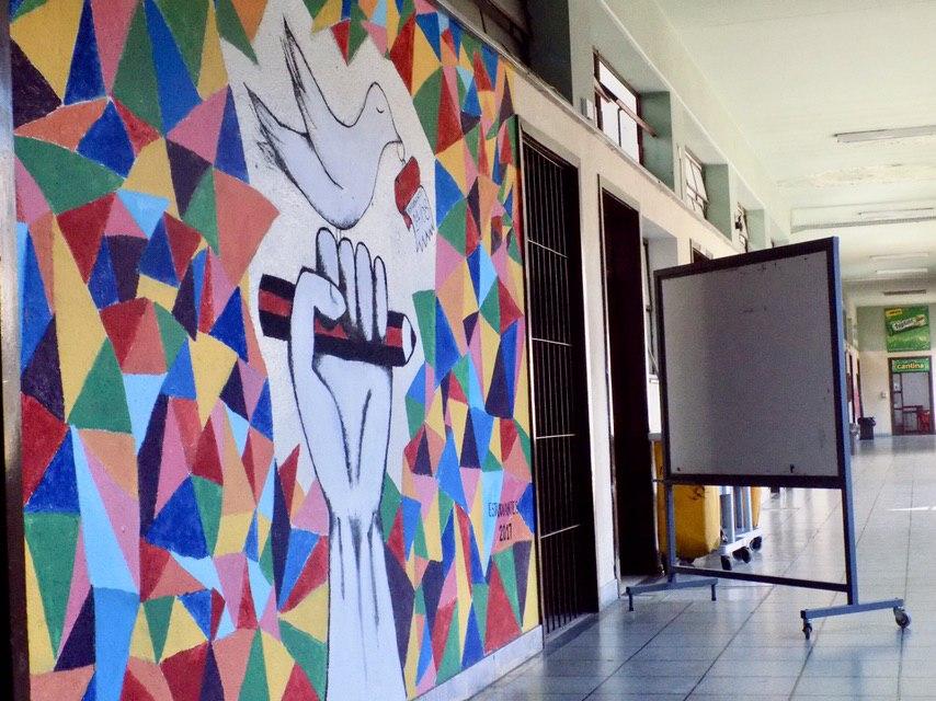 Foto de el pasillo de un liceo. A la derecha hay un pizarrón y a la izquierda una pared con un mural que contiene una mano agarrando un lápiz y una paloma