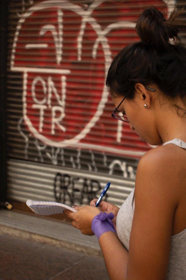 Mujer tomando notas en un block, en la calle.