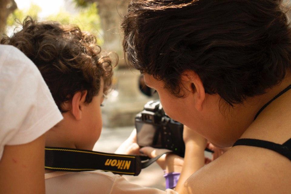 Mujer y niñe observando el visor de una cámara de fotos.