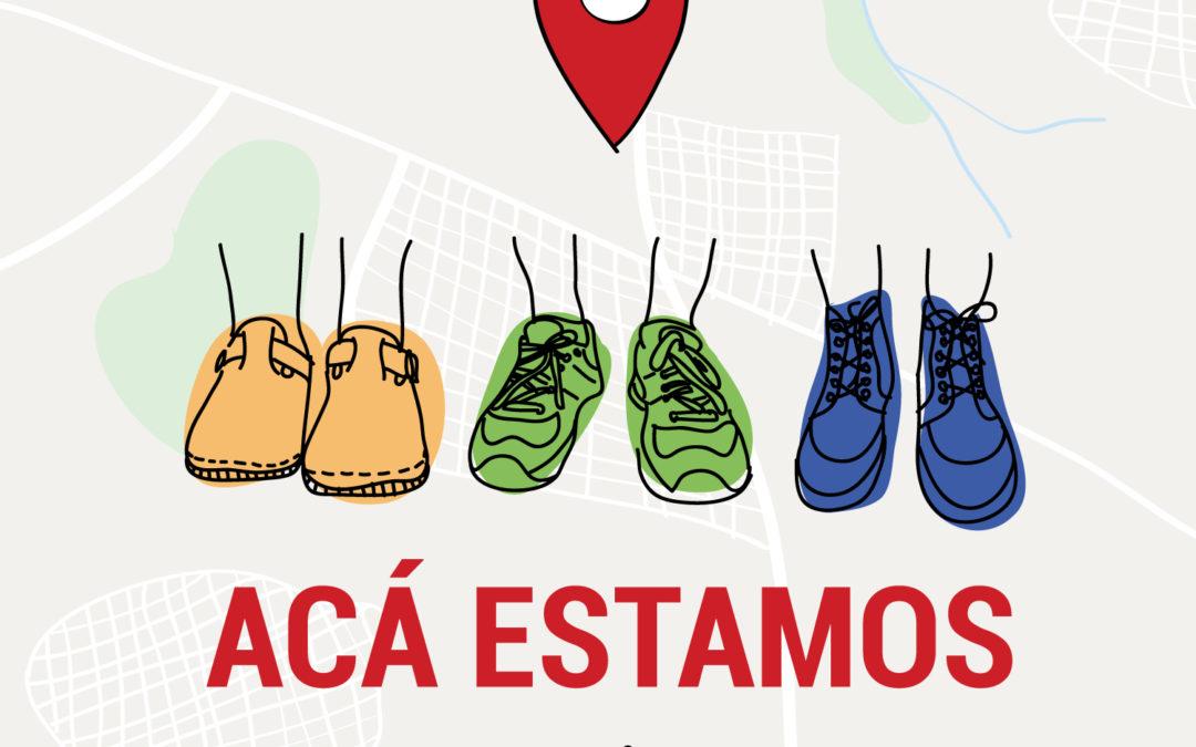 Logo de Acá Estamos: tres pares de pies y un signo de señalización de mapa.
